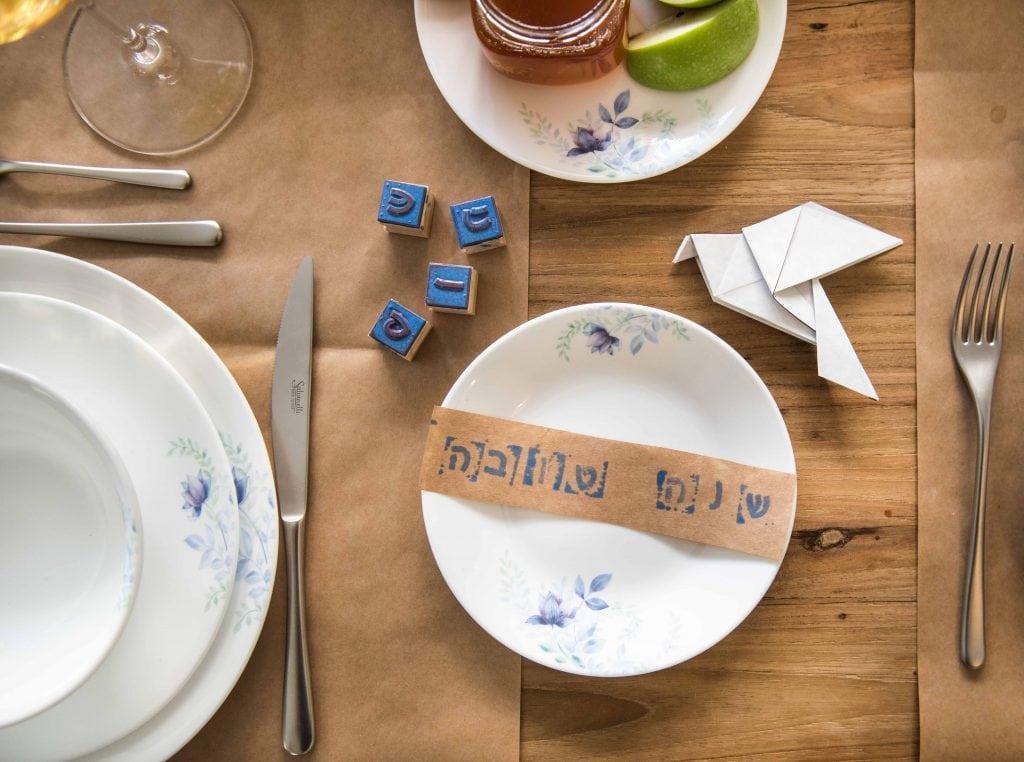 ילדים מקשטים את שולחן ראש השנה עם ברכת שנה טובה מוטבעת עם חותמות  מונחת על כל צלחת