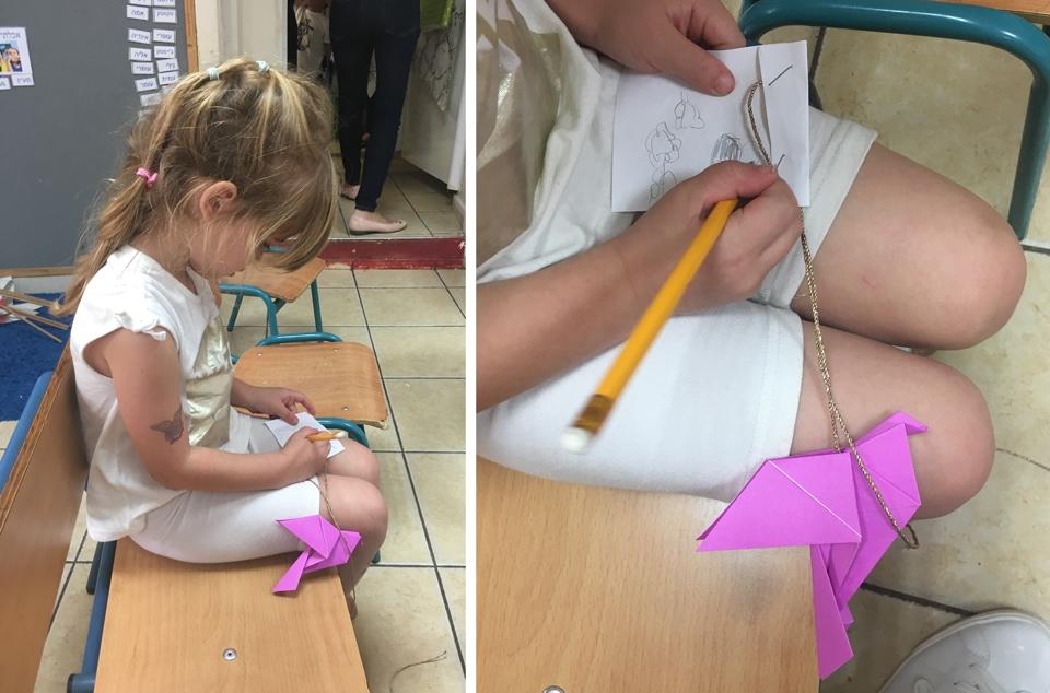 מעיין כותבת ברכה על ציפור האוריגמי שלה